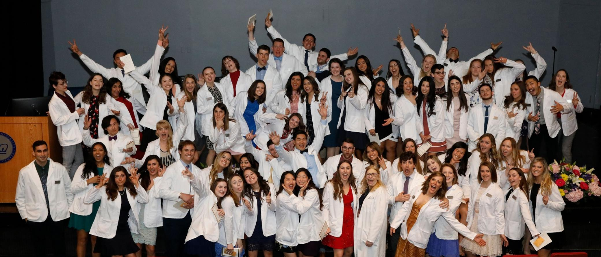 Students on stage with white coats